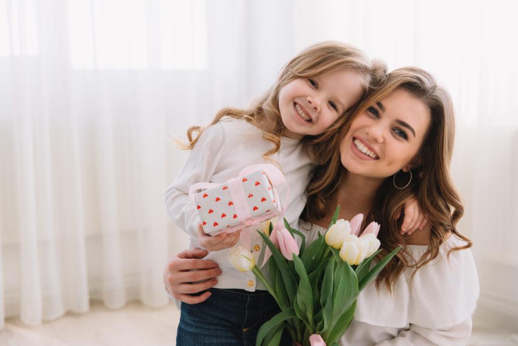 Jolie petite fille qui offre son cadeau à sa maman.